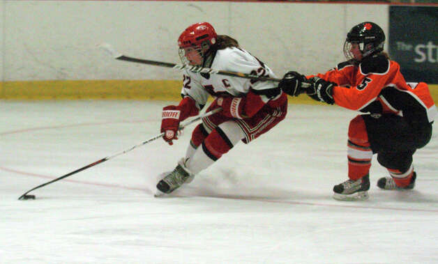 New Canaan's Olivia Hompe cuts through the Ridgefield defense of Heather Ogden, left, and Isabelle Stafford as New Canaan hosts Ridgefield High School in a girls hockey game at the Darien Ice Rink in Darien, Conn., Jan. 19, 2013. Photo: Keelin Daly / Stamford Advocate Riverbend Stamford, CT