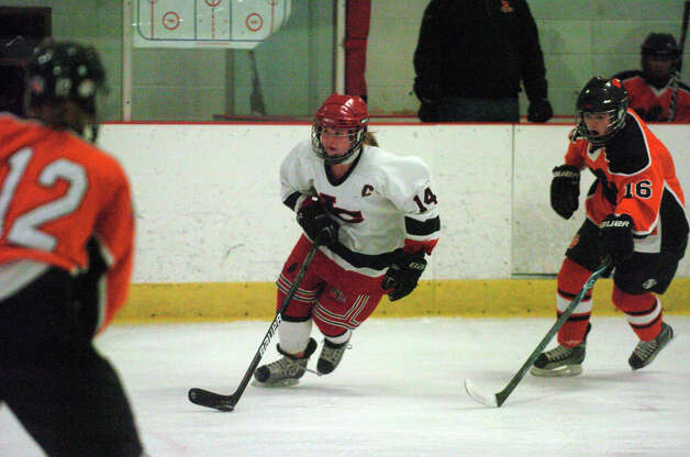 New Canaan's Madzie Carroll moves the puck as Ridgefield's Maeve Reilly, right, closes in New Canaan hosts Ridgefield High School in a girls hockey game at the Darien Ice Rink in Darien, Conn., Jan. 19, 2013. Photo: Keelin Daly / Stamford Advocate Riverbend Stamford, CT