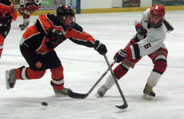New Canaan's Emma Rosenstein fires as Ridgefield's Kate Lombardozzi blocks as New Canaan hosts Ridgefield High School in a girls hockey game at the Darien Ice Rink in Darien, Conn., Jan. 19, 2013. Photo: Keelin Daly / Stamford Advocate Riverbend Stamford, CT