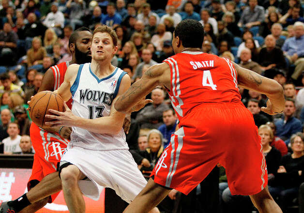 Timberwolves guard Luke Ridnour breaks through the defense of Rockets guard James Harden and forward Greg Smith. Photo: Stacy Bengs, Associated Press / FR170489 AP