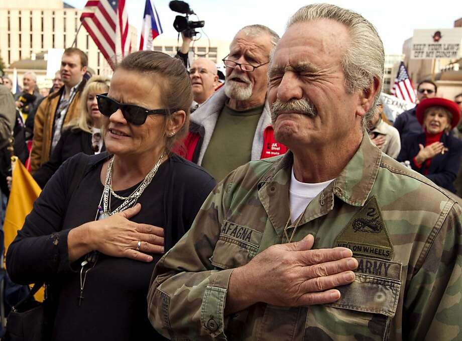 Rafael Cafagna, right, becomes emotional while standing with his wife, Shannon Cafagna, left, during the singing of the national anthem at the Guns Across America rally at the state Capitol in Austin, Texas, on Saturday Jan. 19, 2013. Several hundred people attended the pro-Second Amendment rally. Photo: Jay Janner, Associated Press