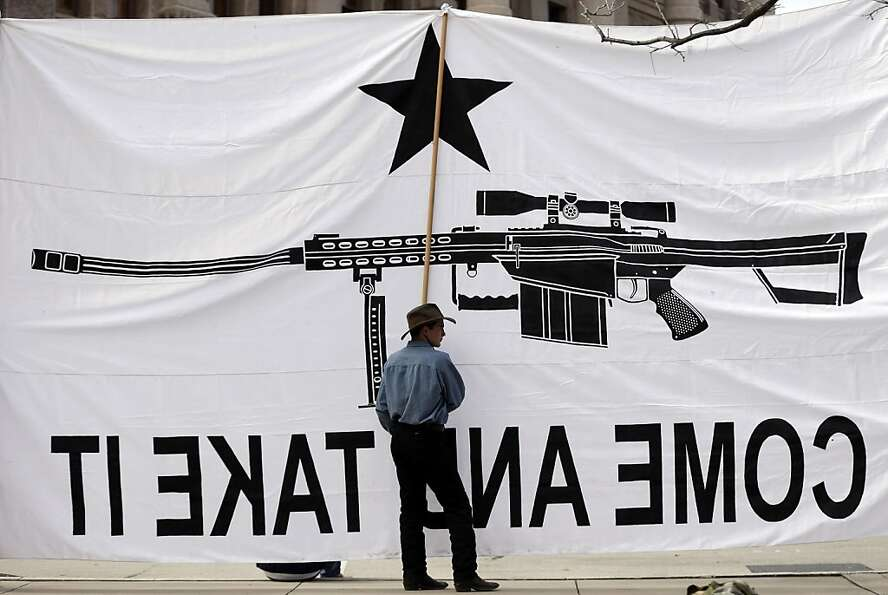 Austin Ehlinger helps hold a banner during a Guns Across America rally at the Texas state Capitol, S