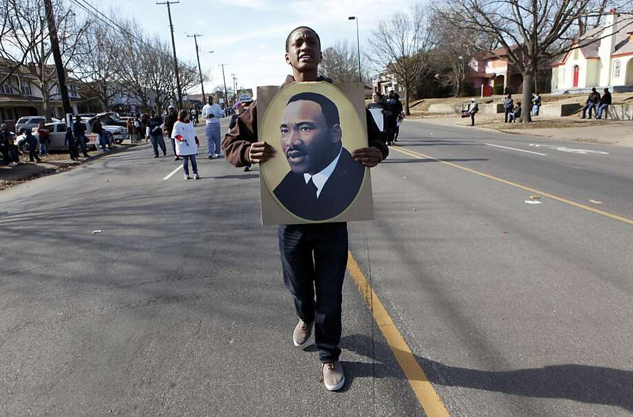 Jordan Young marches with a portrait of Martin Luther King Jr. during the MLK Birthday Celebration March/Parade on Martin Luther King Jr. Blvd. in Dallas on Saturday, Jan. 19, 2013. Photo: Lara Solt, Associated Press