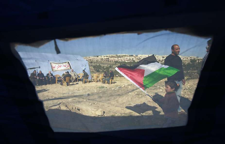 Palestinian activists stand by the tents in the village of Beit Iksa in the West Bank, between Ramal