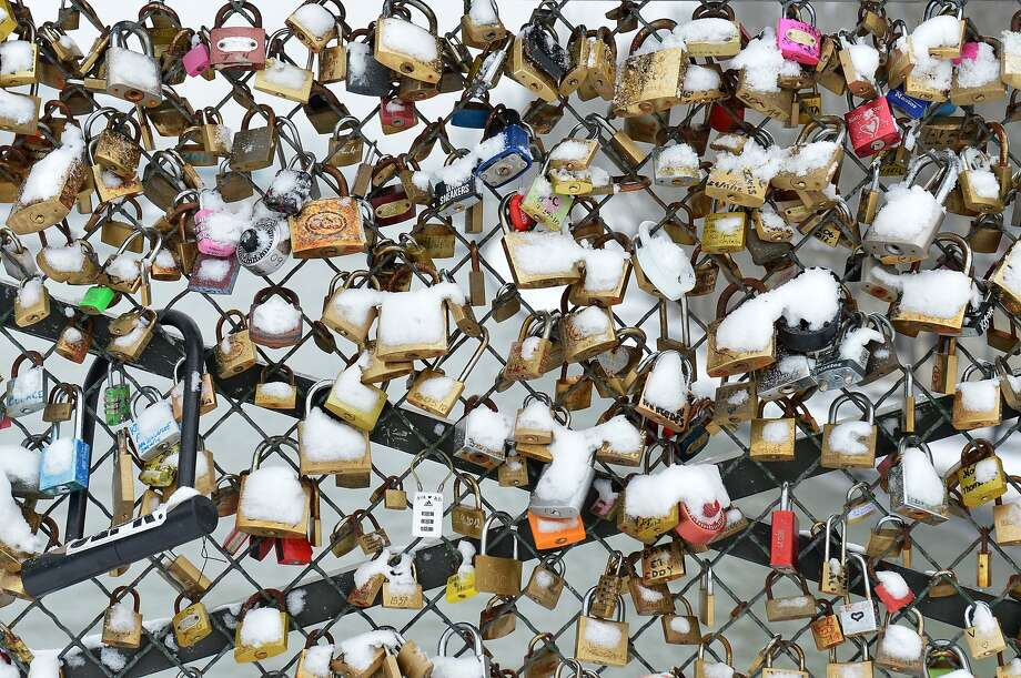 Padlocks (locks of love) are covered with snow on the Pont des Arts bridge on January 19, 2013 in Paris. Photo: Miguel Medina, AFP/Getty Images