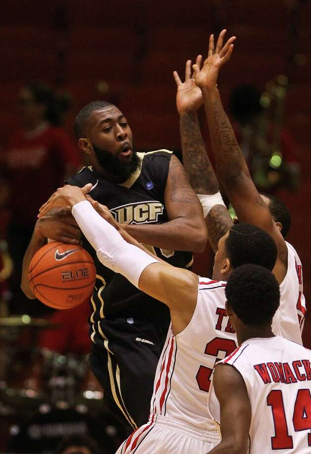 Houston's TaShawn Thomas gets a little more than the ball as he defends against UCF's Keith Clanton in the second half. Photo: Nick De La Torre, Staff / © 2013  Houston Chronicle