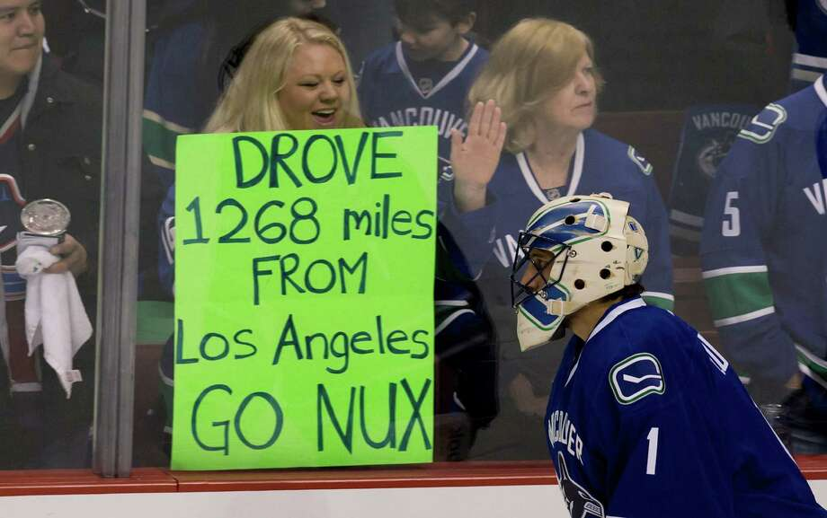 The NHL season opened Saturday, much to the delight of fans, especially this one who had a message for Vancouver Canucks goalie Roberto Luongo. Photo: Darryl Dyck, SUB / The Canadian Press