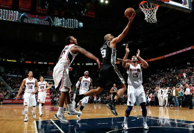 Tony Parker (9) of the Spurs drives between Jeff Teague (0) and Al Horford (15) of the Hawks at Philips Arena on Jan. 19, 2013 in Atlanta. Photo: Kevin C. Cox, Getty Images / 2013 Getty Images