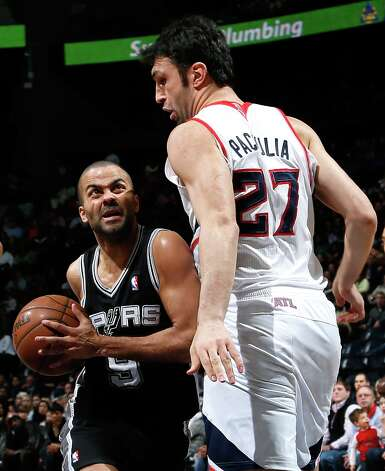 Tony Parker (9) of the Spurs drives against Zaza Pachulia (27) of the  Hawks at Philips Arena on Jan. 19, 2013 in Atlanta. Photo: Kevin C. Cox, Getty Images / 2013 Getty Images