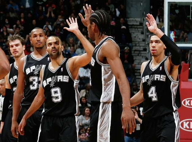 The Spurs' Tony Parker (9) celebrates with Kawhi Leonard (2) and Danny Green (4) after a basket in the final seconds against the Hawks at Philips Arena on Jan. 19, 2013 in Atlanta. Photo: Kevin C. Cox, Getty Images / 2013 Getty Images