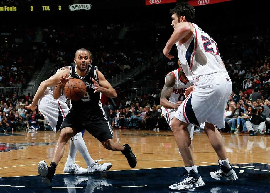 Tony Parker (9) of the Spurs drives between Kyle Korver (26), Jeff Teague (0) and Zaza Pachulia (27) of the Hawks at Philips Arena on Jan. 19, 2013 in Atlanta. Photo: Kevin C. Cox, Getty Images / 2013 Getty Images