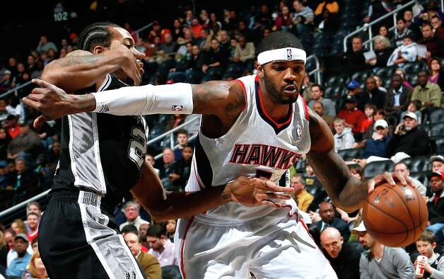 Josh Smith (5) of the Hawks drives around Kawhi Leonard of the Spurs at Philips Arena on Jan. 19, 2013 in Atlanta. Photo: Kevin C. Cox, Getty Images / 2013 Getty Images