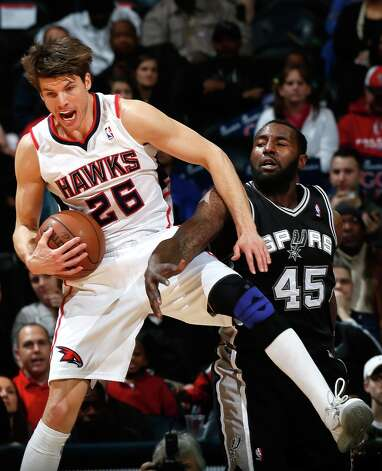 Kyle Korver (26) of the Hawks grabs a rebound against DeJuan Blair of the Spurs at Philips Arena on Jan. 19, 2013 in Atlanta. Photo: Kevin C. Cox, Getty Images / 2013 Getty Images
