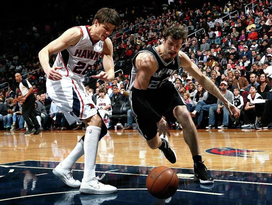 Tiago Splitter (22) of the Spurs steals the ball from Kyle Korver (26) of the Hawks at Philips Arena on Jan. 19, 2013 in Atlanta. Photo: Kevin C. Cox, Getty Images / 2013 Getty Images