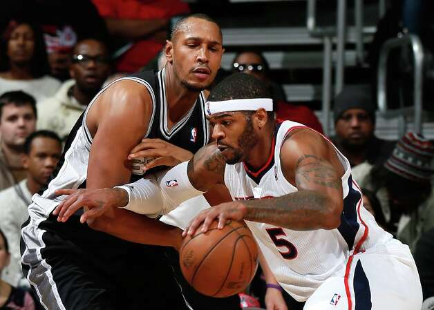 Josh Smith (5) of the Hawks drives against Boris Diaw (33) of the Spurs at Philips Arena on Jan. 19, 2013 in Atlanta. Photo: Kevin C. Cox, Getty Images / 2013 Getty Images