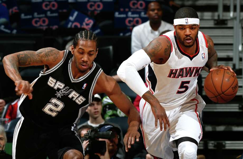 Josh Smith (5) of the Hawks grabs a rebound against Kawhi Leonard of the  Spurs at Philips Arena on Jan. 19, 2013 in Atlanta. Photo: Kevin C. Cox, Getty Images / 2013 Getty Images