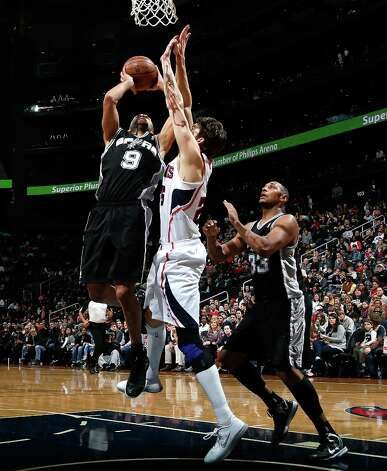 Tony Parker (9) of the Spurs shoots against Kyle Korver (26) of the  Hawks at Philips Arena on Jan. 19, 2013 in Atlanta. Photo: Kevin C. Cox, Getty Images / 2013 Getty Images