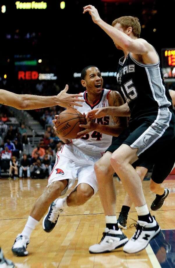 Hawks guard Devin Harris (34) drives against Spurs forward Matt Bonner (15) in the second  half Saturday, Jan. 19, 2013, in Atlanta.  San Antonio won 98-93. Photo: John Bazemore, Associated Press / AP