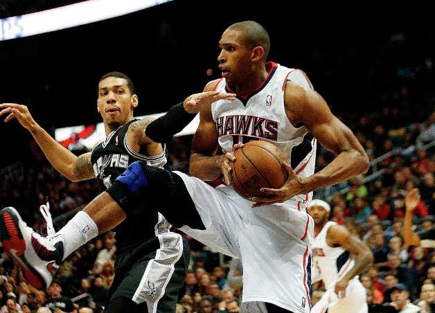 Hawks center Al Horford (15) grabs a rebound against Spurs guard Danny Green (4) in the first half  Saturday, Jan. 19, 2013, in Atlanta. Photo: John Bazemore, Associated Press / AP