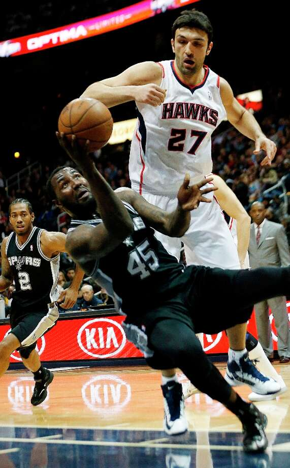 Spurs center DeJuan Blair (45) falls as he shoots in front of Hawks center Zaza Pachulia (27) in the first half Saturday, Jan. 19, 2013, in Atlanta. Photo: John Bazemore, Associated Press / AP