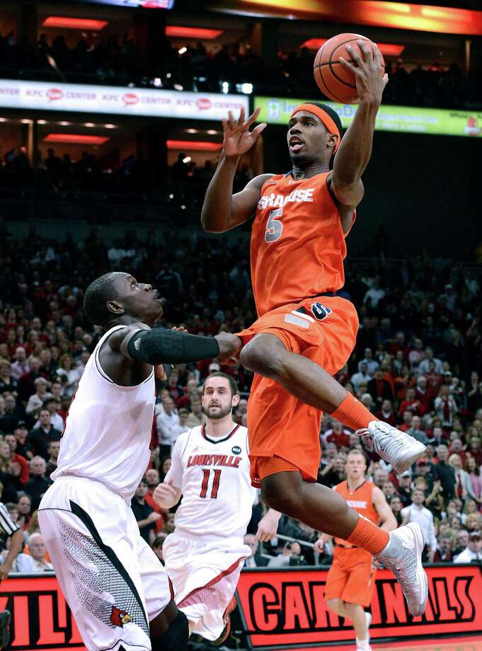Syracuse's C.J. Fair, right, shoots against Louisville's Gorgui Dieng during the first half of an NCAA college basketball game Saturday Jan. 19, 2013, in Louisville, Ky. (AP Photo/Timothy D. Easley) Photo: Timothy D. Easley