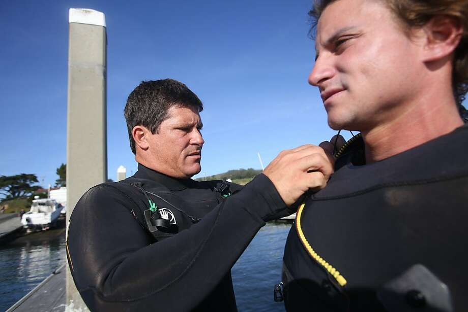 On the day before the Mavericks Invitational, contestant Dave Wassel, left, helps Alex Gray suit up before a practice session on Saturday, January 19, 2013. Photo: Mathew Sumner, Special To The Chronicle