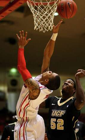 Houston guard Joseph Young, left, quickly puts ball into the hoop after a rebound as Central Florida's Stephon Blair watches. Photo: Nick De La Torre, Houston Chronicle / © 2013  Houston Chronicle