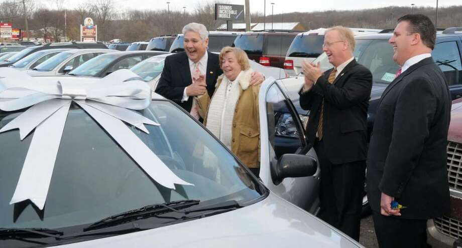 Virginia George, 2nd from left, of Danbury, CT, was given a late model car by Raymond Beylouni, left, and his son, David Beylouni, right, of Colonial Automotive Group, in Danbury, CT, on Wednesday, Dec. 23, 2009. Mayor Mark Boughton was also on hand, 2nd from right. George's home and car were destroyed in a fire last week. When told her car wouldn't be covered, co-workers from Danbury Town Hall and members of the Danbury Fire Department took up a collection.  Word got to the Beylouni's and they quickly donated the car. Photo: Jay Weir / The News-Times