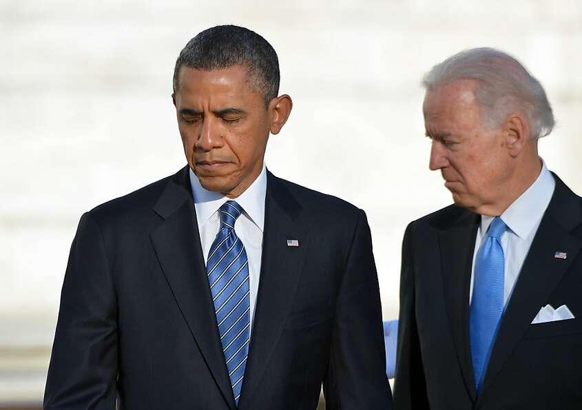 US President Barack Obama and Vice President Joe Biden leave after laying a wreath at the Tomb of th