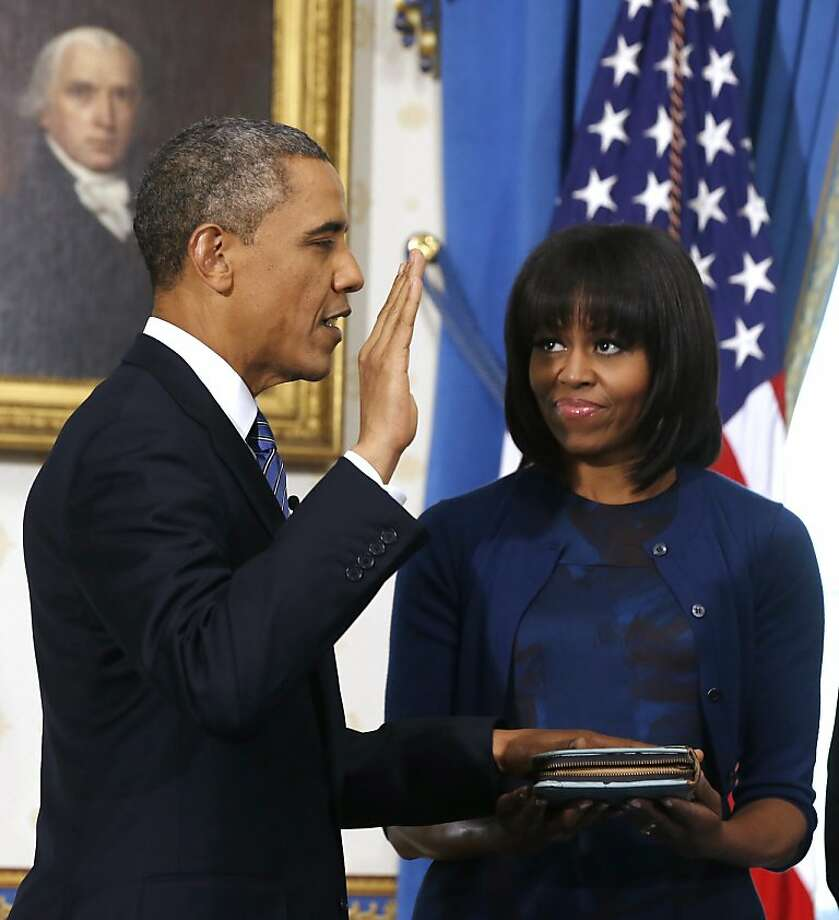 President Barack Obama is officially sworn-in by Chief Justice John Roberts in the Blue Room of the White House during the 57th Presidential Inauguration in Washington, Sunday Jan. 10, 2013, as first lady Michelle Obama, holds the Robinson Family Bible. Photo: Larry Downing, Associated Press