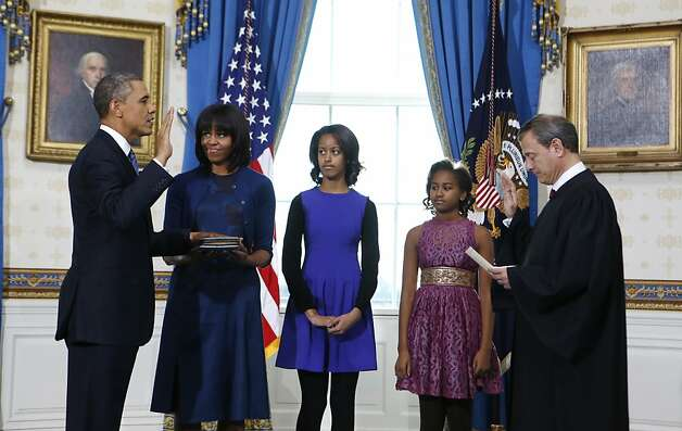President Barack Obama is officially sworn-in by Chief Justice John Roberts in the Blue Room of the White House during the 57th Presidential Inauguration in Washington, Sunday Jan. 10, 2013. Next to Obama are first lady Michelle Obama, holding the Robinson Family Bible, and daughters Malia and Sasha. Photo: Larry Downing, Associated Press