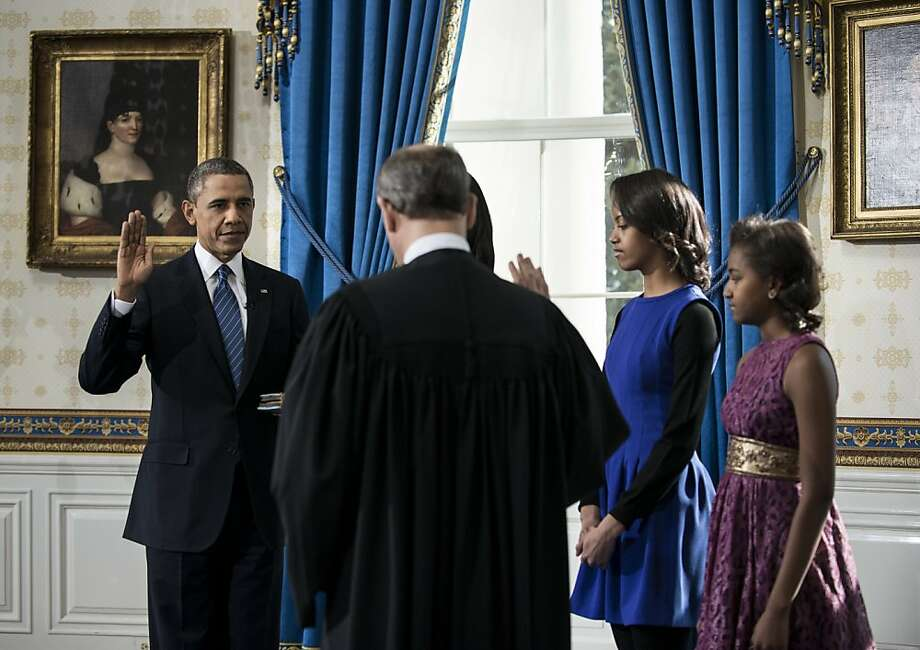 President Barack Obama is officially sworn-in by Chief Justice John Roberts in the Blue Room of the White House during the 57th Presidential Inauguration in Washington, Sunday, Jan. 20, 2013. Next to Obama are first lady Michelle Obama, most obscured, holding the Robinson Family Bible, and daughters Malia and Sasha. Photo: Brendan Smialowski, Associated Press