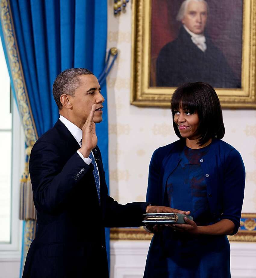 President Obama takes the oath of office at the official swearing-in ceremony in the Blue Room of the White House Sunday, Jan. 20, 2013.  Holding the Bible is first lady Michele Obama. Photo: Doug Mills, Associated Press