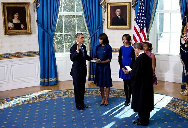 U.S President Barack Obama (L) takes the oath of office as first lady Michelle Obama holds the bible in the Blue Room of the White House January 20, 2013 in Washington, DC. Obama and U.S. Vice President Joe Biden were officially sworn in a day before the ceremonial inaugural swearing-in. Photo: Pool, Getty Images