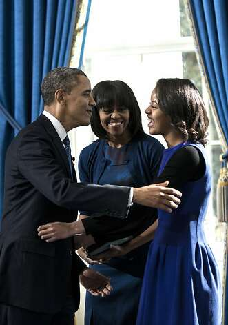 President Barack Obama embraces daughter Malia as first lady Michelle Obama watches after Obama was officially sworn-in by Chief Justice John Roberts, not pictured, in the Blue Room of the White House during the 57th Presidential Inauguration in Washington, Sunday, Jan. 20, 2013. Photo: Brendan Smialowski, Associated Press