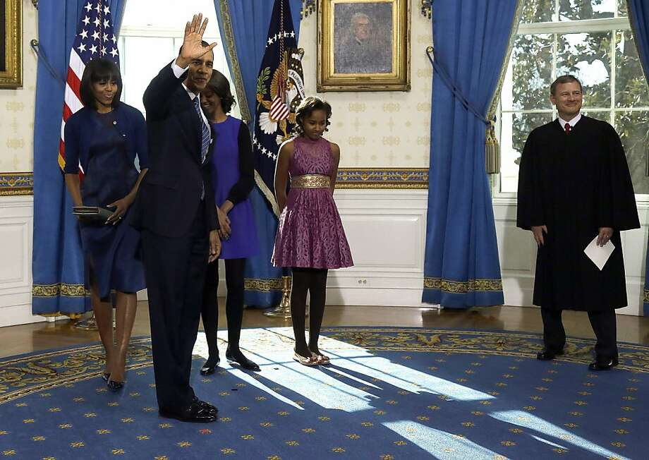 President Barack Obama waves after being  officially sworn-in by Chief Justice John Roberts in the Blue Room of the White House during the 57th Presidential Inauguration in Washington, Sunday, Jan. 20, 2013. Next to Obama are first lady Michelle Obama and daughters Malia and Sasha. Photo: Charles Dharapak, Associated Press