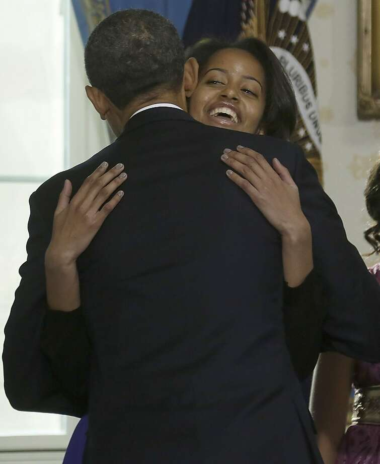 U.S. President Barack Obama is hugged by  daughter Malia after being officially sworn-in in the Blue Room of the White House during the 57th Presidential Inauguration January 20, 2013 in Washington, D.C.  Obama and U.S. Vice President Joe Biden were officially sworn in a day before the ceremonial inaugural swearing-in. Photo: Pool, Getty Images