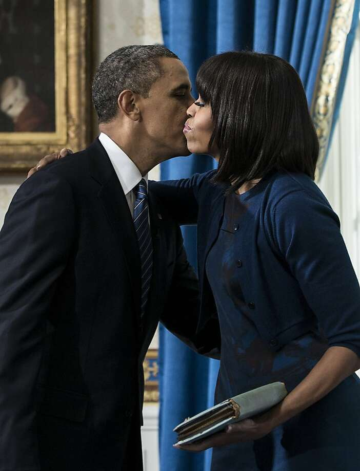 President Barack Obama kisses first lady Michelle Obama after being officially sworn-in by Chief Justice John Roberts in the Blue Room of the White House during the 57th Presidential Inauguration in Washington, Sunday, Jan. 20, 2013. Photo: Brendan Smialowski, Associated Press