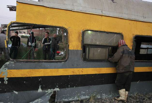 Egyptians railway workers and bystanders inspect wreckage following a train crash in Badrasheen, 40 KM south of Cairo, Egypt, Tuesday. At least 19 people died and more than 100 were injured when two railroad passenger cars derailed just south of Cairo, health officials say. The accident comes less than two weeks after a new transportation minister was appointed to overhaul the rail system, and just two months after a deadly collision between a train and school bus. Photo: AP