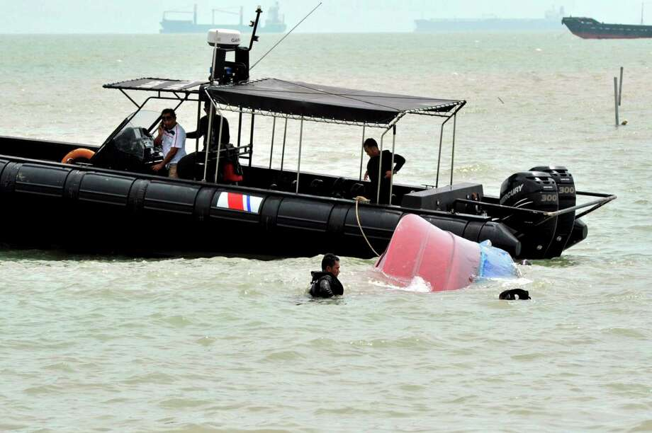 Malaysian Maritime Enforcement Agency enforcement officers retrieve a capsized boat on Monday in Pengerang, Johor, Malaysia. Malaysia's coast guard has rescued 41 Indonesians and is searching for seven others after the boat overloaded with suspected illegal migrants capsized in choppy waters.  Photo: AP
