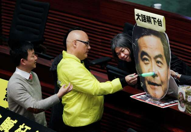 "Hong Kong pro-democracy lawmakers from right, Leung Kwok-hung, Albert Chan and Raymond Wong set up a cutout of the head of Chief Executive Leung Chun-ying with ""Pinocchio's nose"" and a sign which reads ""Liar steps down"" before Chief Executive Leung Chun-ying delivering his policy address at the Legislative Council in Hong Kong Wednesday. Leung Chun-ying focused on the social problems such as housing, pollution and economic development for the next five years. Photo: AP"