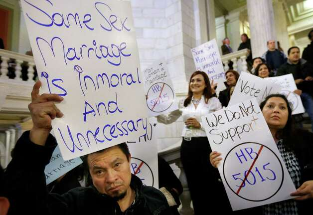 Carlos Perez, of Providence, R.I., left, displays a placard as he joins with other demonstrators opposed to same-sex marriage during a rally at the Statehouse, in Providence, Tuesday. The Rhode Island House Judiciary Committee began hearing testimony from supporters and opponents of same-sex marriage Tuesday. Photo: AP
