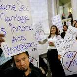 Carlos Perez, of Providence, R.I., left, displays a placard as he joins with other demonstrators opposed to same-sex marriage during a rally at the Statehouse, in Providence, Tuesday. The Rhode Island House Judiciary Committee began hearing testimony from supporters and opponents of same-sex marriage Tuesday.