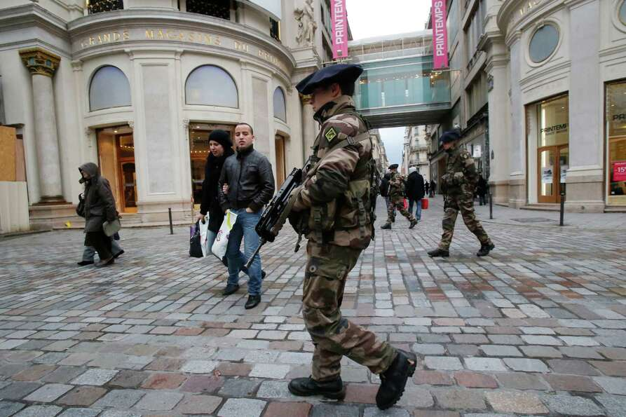 French army soldiers patrol along a main department store in Paris, Tuesday. Armed soldiers are on p