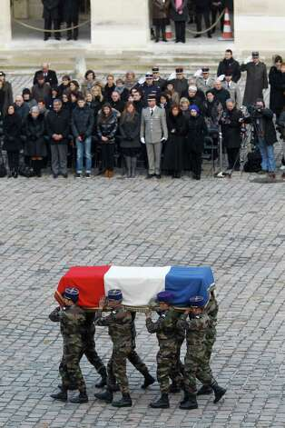 Soldiers carry the coffin of French army lieutenant Damien Boiteux who was killed during a mission in Mali; during a ceremony at the Invalides in Paris, Tuesday. The French pilot died while taking part Friday afternoon in an aerial operation targeting a terrorist group moving on the town of Mopti. Relatives are standing in background. Photo: AP