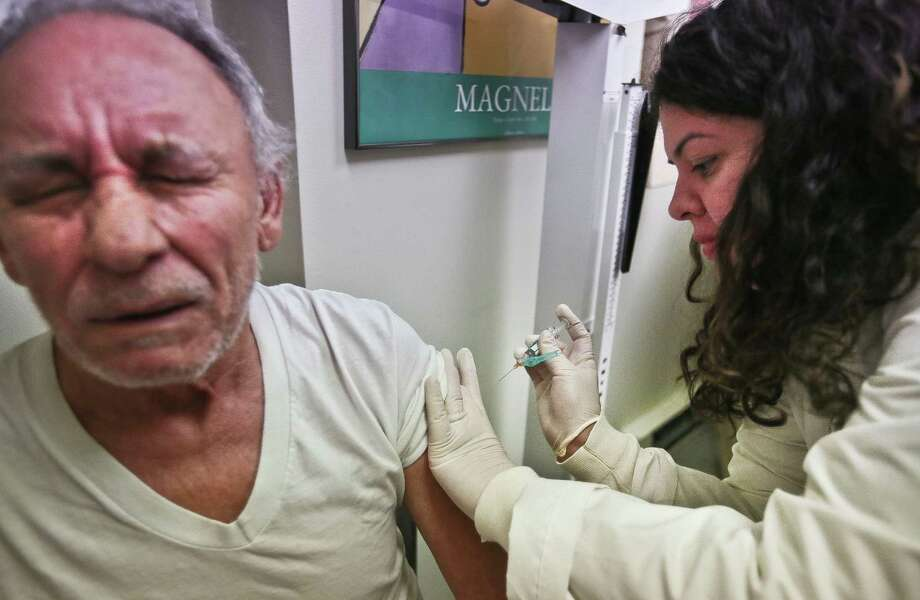 """Carlos Maisonet, 73, reacts as Dr. Eva Berrios-Colon, a professor at Touro College of Pharmacy, injects him with flu vaccine on Tuesday during a visit to the faculty practice center at Brooklyn Hospital in New York.  """"This is his first time getting the flu shot,"""" said Zulma Ramos, Maisonet's wife, who was vaccinated last August.  """"Seniors have a higher risk for getting the flu,"""" said Dr. Berrios-Colon, as she advised Maisonet to get his next vaccine months earlier at the start of the flu season.  State health officials say flu vaccine is still available for New Yorkers who want to get a flu shot, though there may be some localized shortages because of late season demand. Photo: AP"""