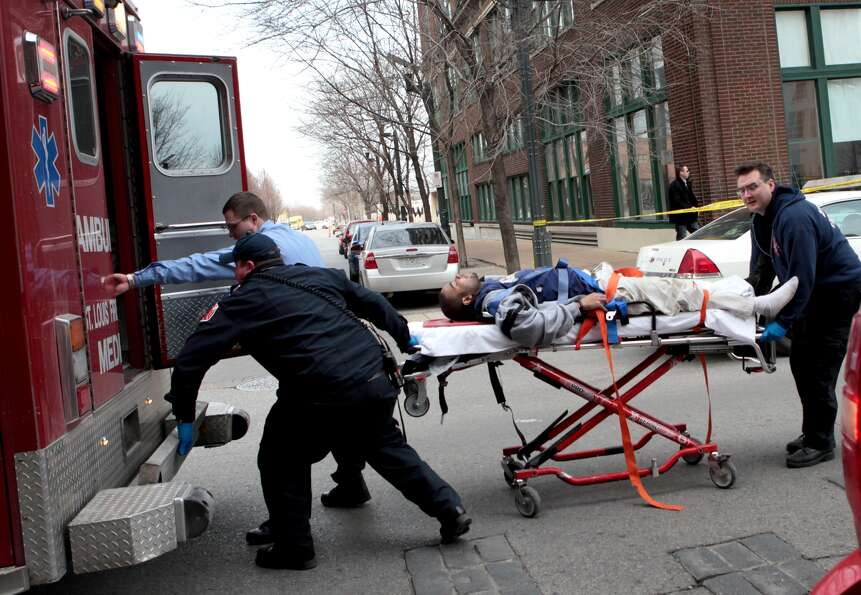 Police and emergency personnel transport a man to an ambulance after a shooting at Stephens Institut