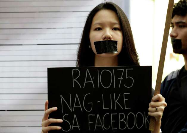 Protesters, with their mouths taped, gather at the Philippine Supreme Court for a rally to coincide with the oral arguments to seek the extension of a temporary restraining order issued by the High Court on the new Cybercrime Law on Tuesday in Manila, Philippines. Bloggers, civil society groups and other organizations converged at the Supreme Court to remind justices of certain provisions of the law which they fear might be used as a tool to target progressive individuals especially if they post their political opinions on the Internet. Photo: AP