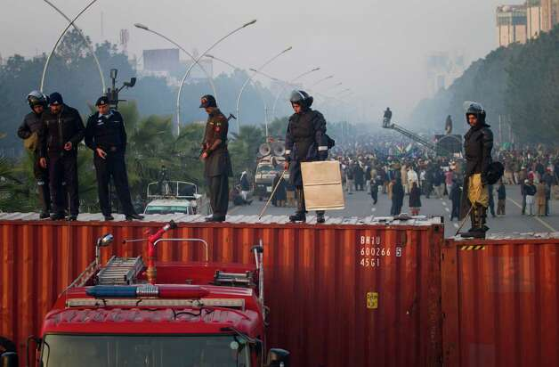 Pakistani police officers stand guard atop shipping containers while supporters of Pakistan Sunni Muslim cleric Tahir-ul-Qadri atage an anti government rally in Islamabad, Pakistan on Tuesday. Thousands of anti-government protesters are rallying in the streets of Pakistani capital for second day despite early-morning clashes with police who fired off shots and tear gas to push back stone-throwing demonstrators. Photo: AP