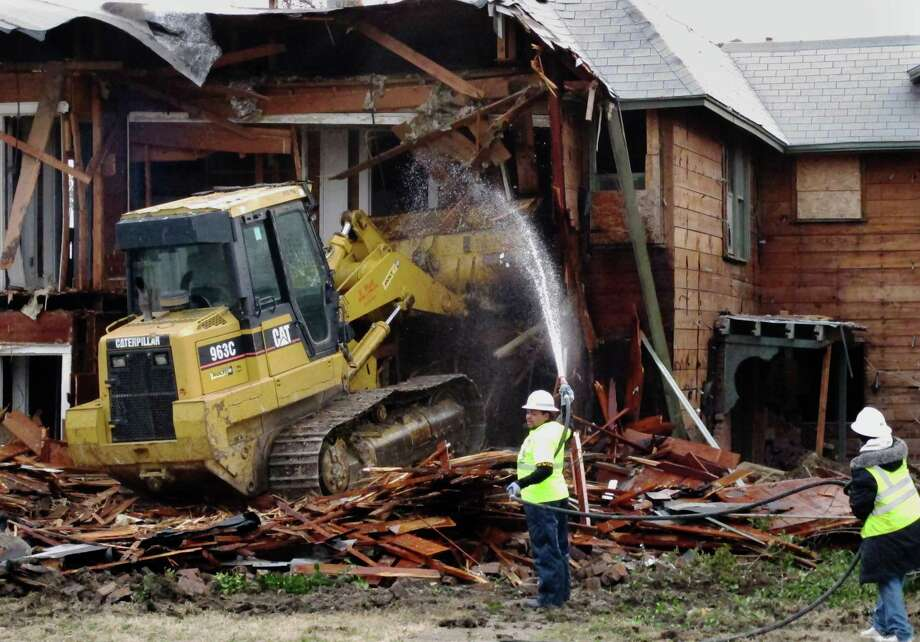 A bulldozer is used to demolish a two-story apartment building  in Dallas, Texas on Monday where Lee Harvey Oswald briefly lived before assassinating President John F. Kennedy. The rundown building was demolished by court order after a dispute between the city and landlord Jane Bryant. Photo: AP